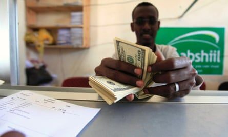 A worker counts U.S. dollars as he serve a customers at a Dahabshiil money transfer office in
