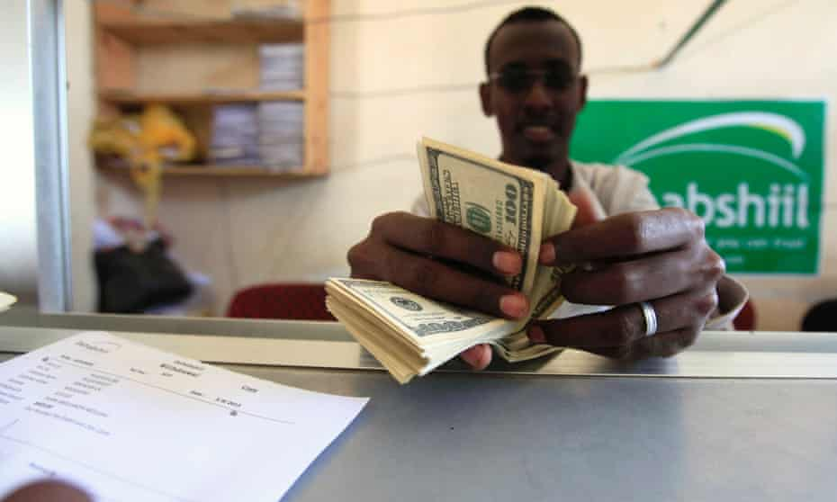 """A worker counts U.S. dollars as he serve a customers at a Dahabshiil money transfer office in """"Kilometer Five"""" street of Soobe village, southern Mogadishu, in this May 8, 2013 file photo. About 40 percent of all Somali families rely on remittances from another country, and the estimated annual total of $1.3 billion is more than all foreign aid and investment in Somalia combined."""