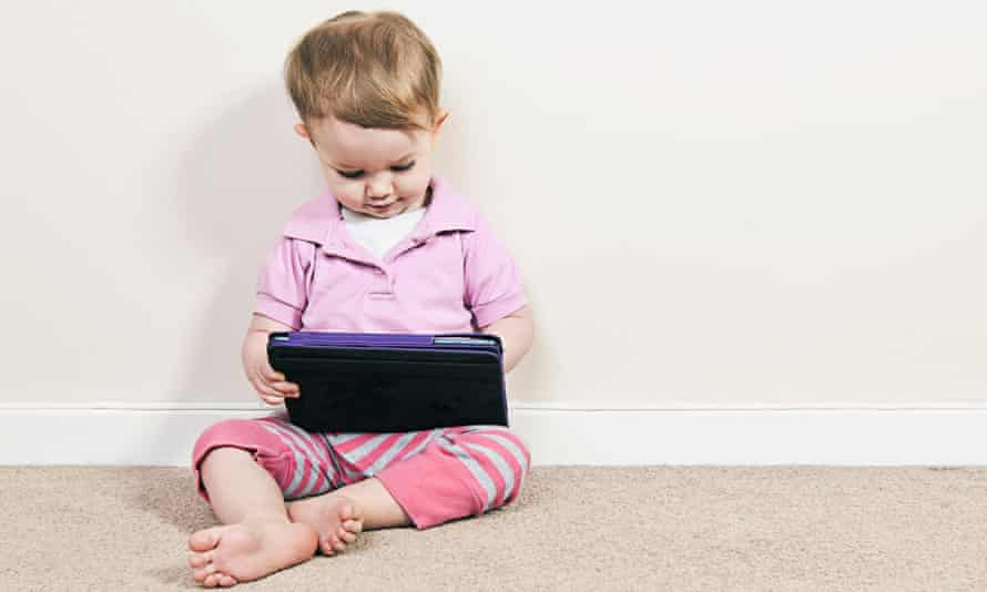 Baby girl plays with ipad.