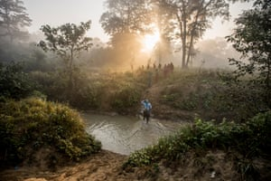 Women cross a river on their way to work in a forest in Nepal