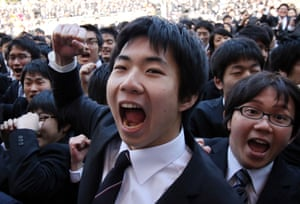Tokyo, Japan College students raise their fists in the air and yell to kick off a ceremony marking the start of the job hunting season. Some 1,500 students, who will graduate from schools in March 2016, attended the annual ceremony which aims to encourage future graduates to look for employment