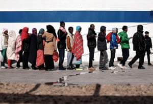 Lampedusa, Italy Migrants wait at the port to board a ferry bound for Porto Empedocle in Sicily. Authorities on the Italian island of Lampedusa struggled to cope with a huge influx of newly-arrived migrants as aid organisations warned the Libya crisis means thousands more could be on their way
