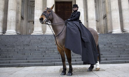 A horsewoman in an outfit designed by Sarah Burton stands outside the cathedral.