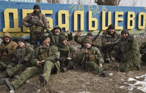 Debaltseve, Ukraine Russia-backed rebels pose by a road sign, after checking the access road into town for mines left behind by retreating Ukrainian government troops. After weeks of relentless fighting, the embattled Ukrainian rail hub of Debaltseve fell Wednesday to Russia-backed separatists