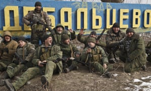 Russia-backed rebels pose by a road sign at the entrance to Debaltseve
