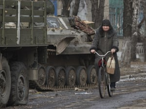 A resident rides a bicycle passing by an armoured vehicle in Debaltseve.