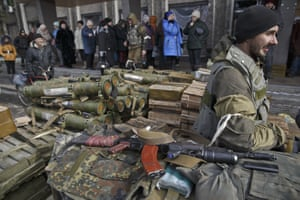 Residents line up waiting for a delivery of aid as a Russia-backed rebel guards a pile of weapons and ammunition outside an administration building