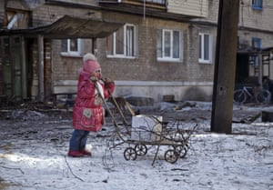 A girl leans on a cart used to carry tree branches for fire, outside a damaged apartment building