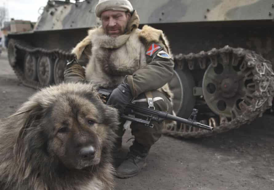 A dog sits next to a Russia-backed rebel near his tank