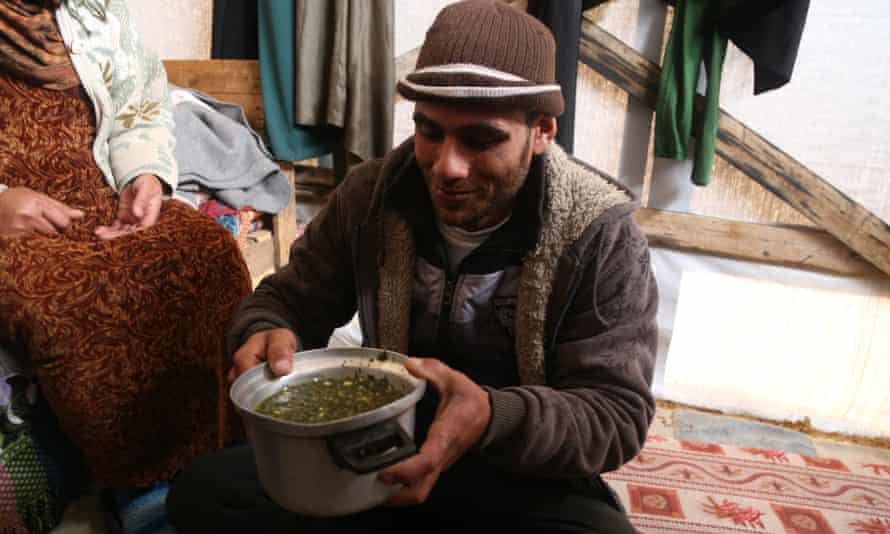 Baby Salma's uncle with the wild grass soup that makes up the majority of the family's diet