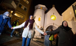 Jews and Muslims hold hands as they join in a ring of solidarity around the synagogue in Oslo, in a peace vigil that drew a crowd of 1,300 people.