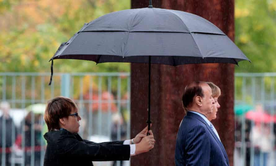 An assistant holds an umbrella above Yemen's president Abd Rabbu Mansour Hadi and German chancellor Angela Merkel in Berlin in 2012.