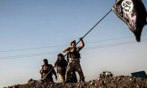 Kurdish border police take down an Isis flag after taking control of Yangija village in September last year