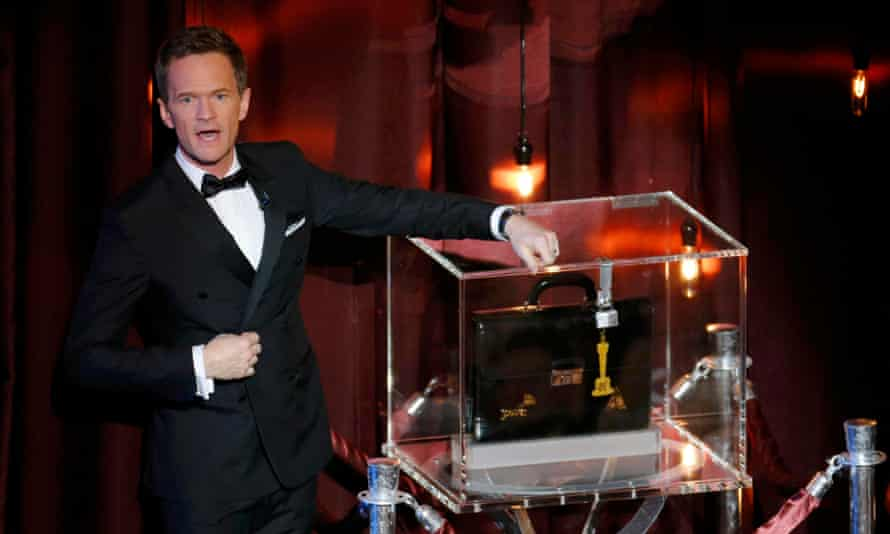 Host Neil Patrick Harris stands next to a sealed briefcase holding his predictions of the Oscar winners.