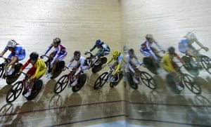 Riders are reflected in a glass pane as they compete during the final of the Women's points race.