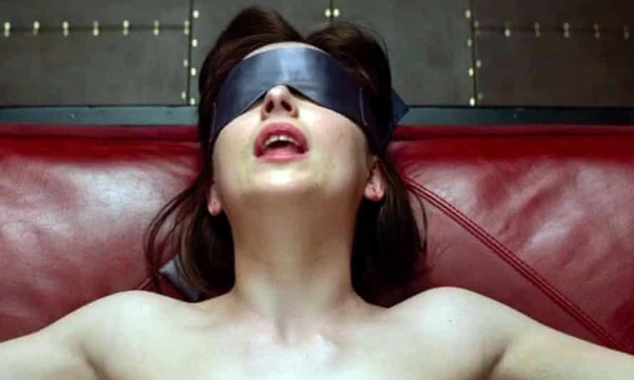 A still from the film of Anastasia Steele (played by Dakota Johnson) wearing a blindfold.