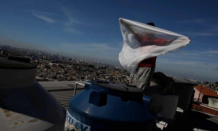A man places a mosquito net over a water container on his roof. Brazilians are hoarding water in their apartments, drilling homemade wells and taking other emergency measures to prepare for forced water rationing.