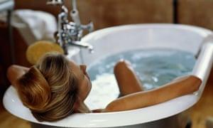 Woman relaxing in roll-top bath
