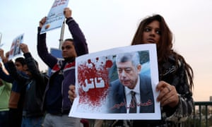 """A demonstrator holds a poster of Mohamed Ibrahim with the word """"Killer"""" on it during a silent protest over a bridge in Cairo earlier this month."""