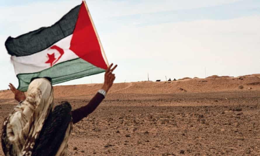 A woman with a Saharawi flag near the so-called Moroccan Wall, a defensive fortification within Western Sahara.