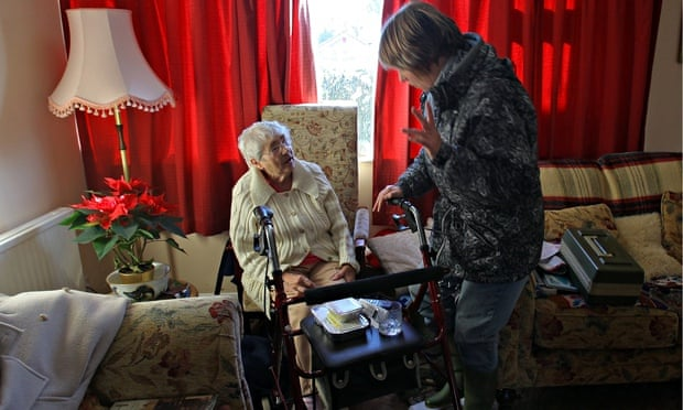 An older woman and gets her meals on wheels delivered to her front room.