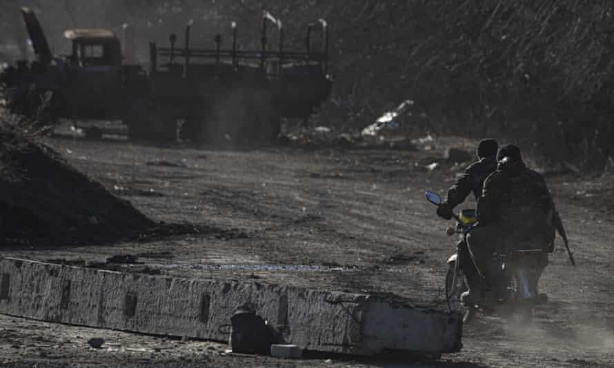 Ukrainian servicemen ride on a motorbike near the village of Luhanske, eastern Ukraine on 24 Februar