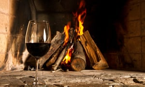 a glass of red wine infront of a fire