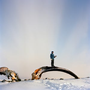 Repulse Bay, Nunavut, Canada. Mike Ivalutanar stands on a giant whalebone and holds a small soapstone carving