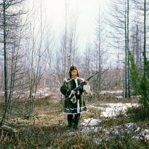 Zhigansk, Sakha Republic, Russia. Maria takes time out from a family picnic to practise her shooting in her traditional Evenk dress