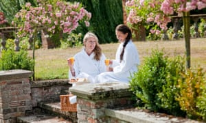 Two smiling women wearing white dressing gowns, holding glasses of orange juice in a pretty garden