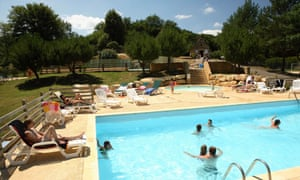 People in a swimming pool and sunbathing around it at Le Val d'Ussel Eurocamp