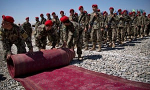 Afghan soldiers in red headgear roll up the red carpet on stony ground