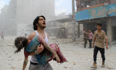 A man carries a girl injured in a reported barrel-bomb attack in Kallaseh district, Aleppo, last year.