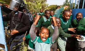 Students from Langata primary school in Nairobi run past riot police as they protest against a perimeter wall illegally erected by a private developer around their school playground in January 2015.