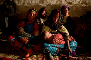 Women hold their babies as they keep warm by the fireside