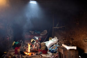 A woman and her children warm themselves around a fire in their home in Tilmi village