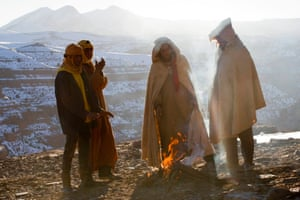Villagers warm themselves around a fire