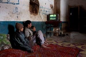 Children watch TV in their house in Tilmi village