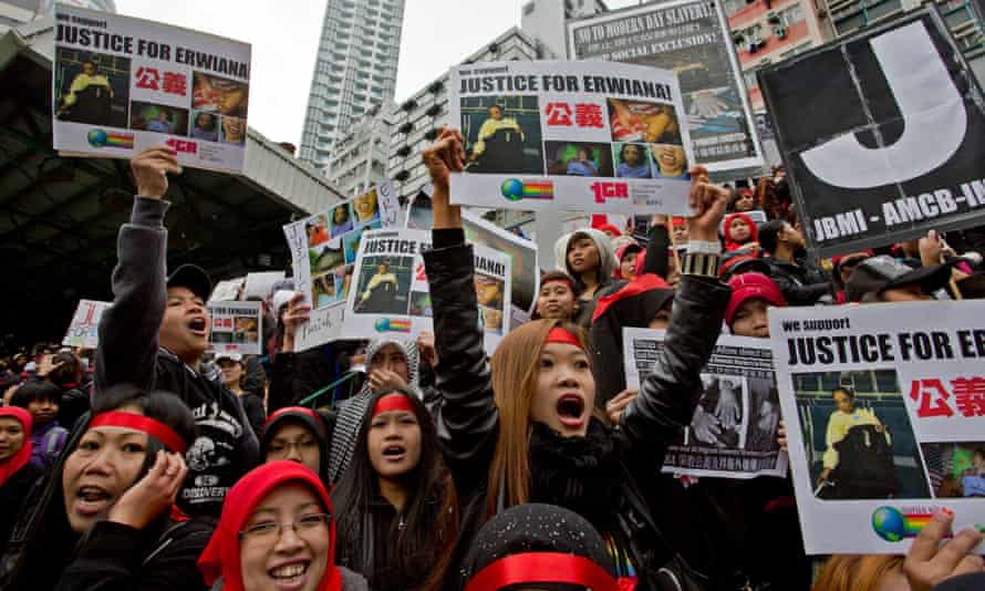 Domestic helpers shout slogans while holding pictures of 23-year-old Indonesian maid Erwiana Sulistyaningsih during a protest in Hong Kong, in January 2014. Erwiana was allegedly assaulted for nearly eight months before the family she worked for sent her back to Indonesia.