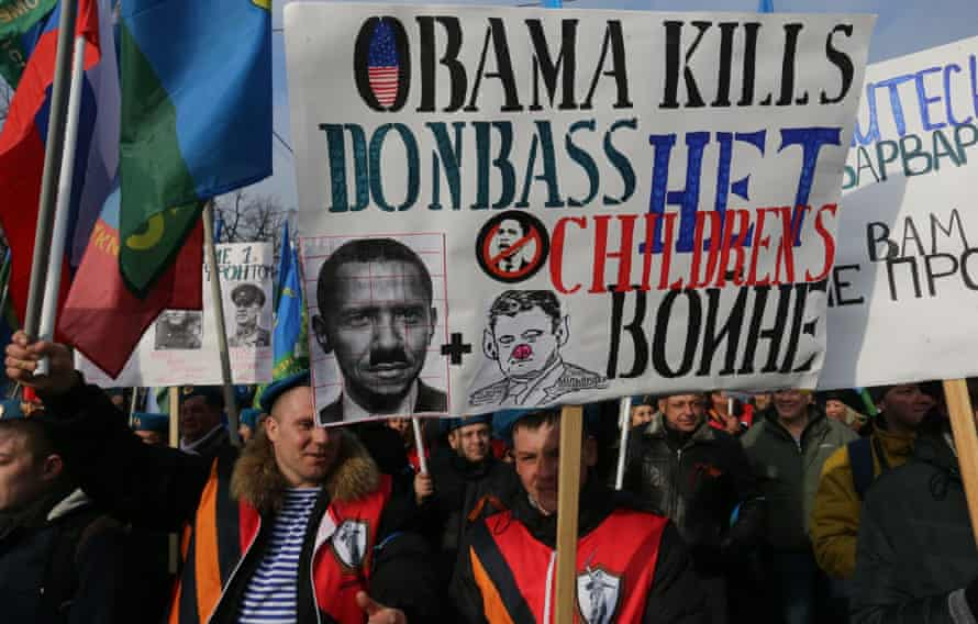 Pro-Kremlin activists from Russia's Anti-Maidan movement march with a sign which says 'Obama kills Donbass'.