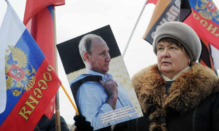 A woman carrying a portrait of Vladimir Putin takes part in an Anti-Maidan rally.