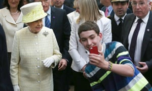 A teenager trying to take a selfie in front of the Queen in Belfast.