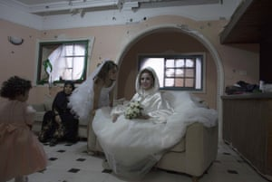 Palestinian bride Anaan El Harazen, 24, sits in the damaged salon of her family's home