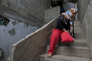 Palestinian woman Safa Fayez, 29, pulls herself up the staircase of her home in Beit Hanoun, Gaza. She was seriously wounded by shrapnel when IDFshells hit a UN school crowded by hundreds of Palestinians seeking shelter. The attack on July 24, 2014 killed at 15 Palestinians and wounded many other, including her baby and husband. She is a mother of four children and said that she had just left the classroom she was staying in with her family and was heading outside to wait for a Red Cross bus when the attack occurred