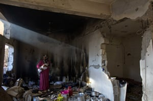 Palestinian woman Ramba Kafanah  stands breastfeeding her newborn baby in the kitchen of her damaged house