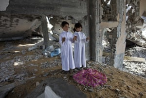 Palestinian brothers Achmed, 5, and Hussama,7, use the top of an umbrella as a prayer carpet amongst the ruins of the Omar Abed El Aziz Mosque in Beit Hanoun during Friday prayers