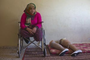 Palestinian Manar Shabari sits in her wheelchair by her prosthetic legs that have been fitted with festive shoes to be worn at her brother's wedding