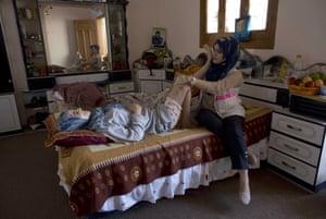 Wounded Palestinian woman Amal el Rafati, 30, receives rehabilitation treatment from a nurse