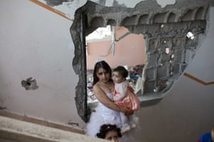 Palestinian children dressed in their party clothes wait for bride Anaan El Harazen, 24, in the family's damaged home as they prepare for a wedding in the Shujai'iya neighbourhood