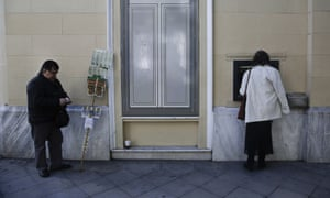 A woman withdraws cash from a ATM in Athens